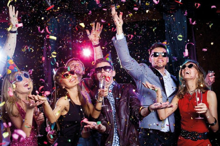 A group of young people wearing themed glasses, dressed for a party and drinking champagne from flutes enjoy confetti and streamers dropping onto them.